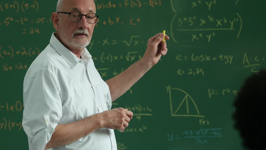 Older man teaching in classroom pointing at diagrams on a blackboard