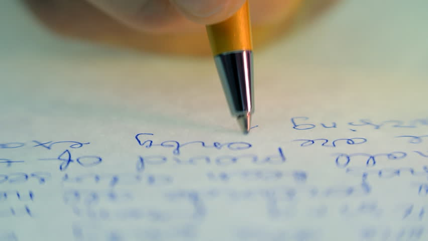 Pen writes a letter on paper. Closeup. Dolly shot. Shallow depth of field