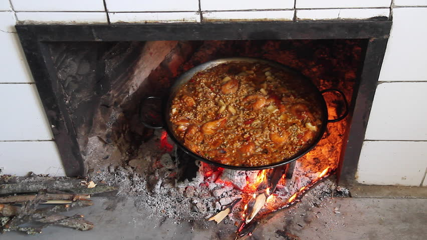 Stock Footage of Cooking a paella - Paella rice cooking on a wood fire in the fireplace in the kitchen