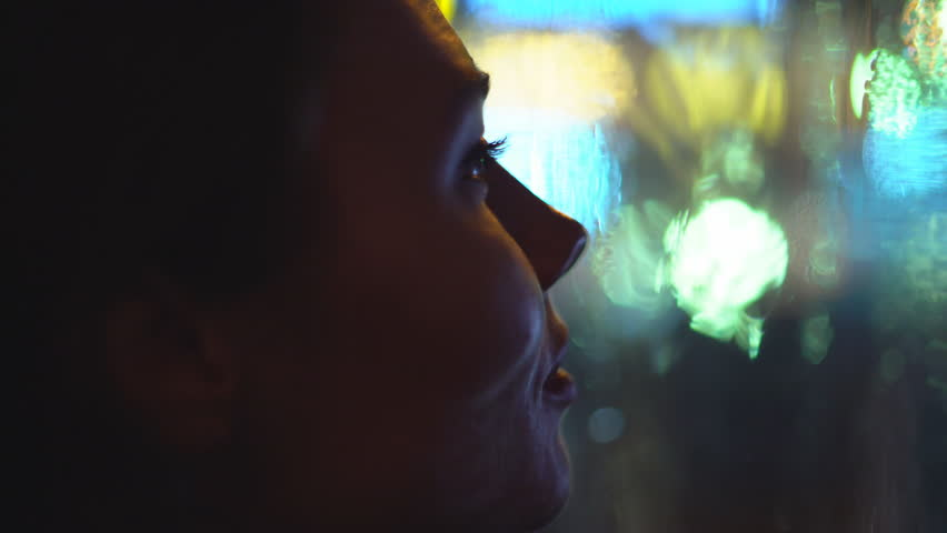 Young attractive woman is sitting by the window. it is raining outside the window. large drops glide across the glass. outside the window the night and the lights of the city and passing cars. a close | Shutterstock HD Video #1005618529