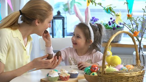 Mother And Daughter eating Chocolate Easter Eggs sitting at the holiday table with a basket and a yellow rabbit. Slow Motion