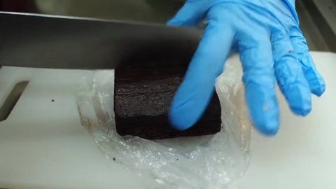 Slicing homemade plain brownie with kitchen knife.