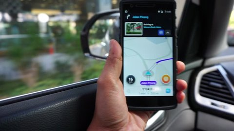 MALAYSIA, Kuala Lumpur, December 19, 2017: The hand is holding a smart phone waze application to show the city's road direction.
