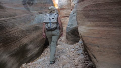 Active woman hiking through the dried up narrow stone gorge of river with smooth and wavy rocks of a colorful canyon zion national park, looks around and expresses emotions slow motion, 4K, 3840X2160