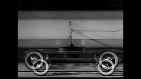 CIRCA - 1938 - Shock absorbers are used in an apparatus with model wheels in a study of bumpy movement in the suspension of a car.