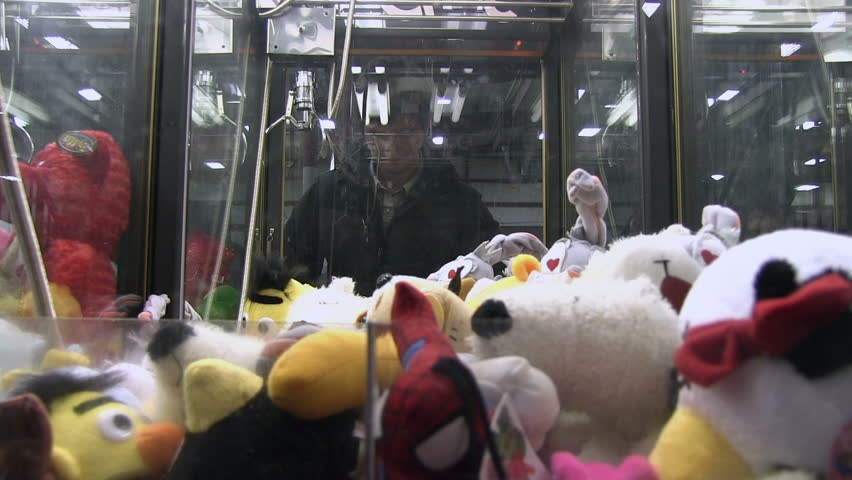 Man playing claw game in reflection