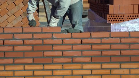 worker builds a wall of bricks in summer day. the builder on a building makes bricklaying. the builder at the construction site makes brickwork. construction? brick laying