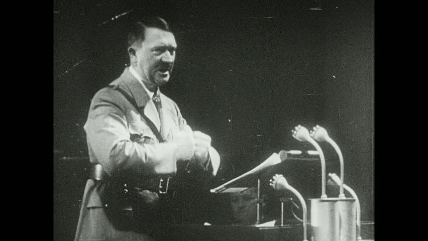 1940s: Adolf Hitler gives speech, gesticulates with closed fists. Fly's head. Tojo stands and gets flashed from cameras. Boll weevil. Bennito gives a speech and stands with his hands on the belt.