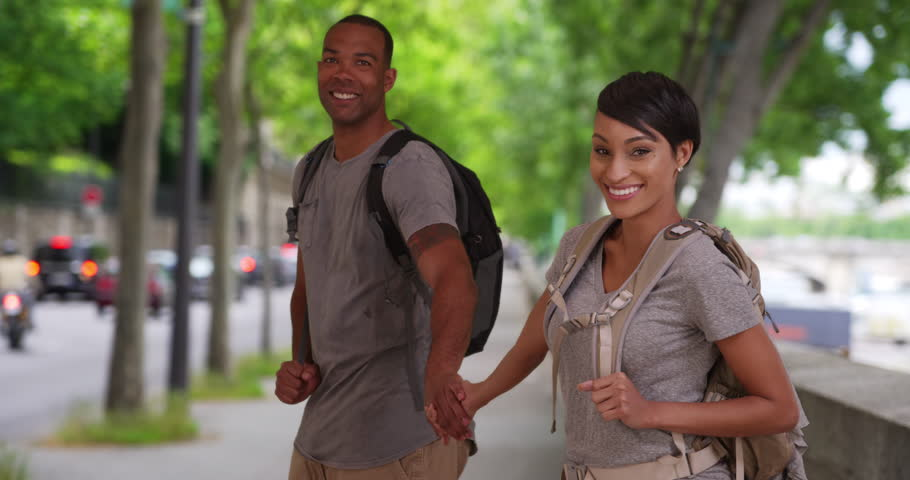 Active African boyfriend and girlfriend wearing backpacks walking around a European city. Happy young tourists in a European setting walk off-screen while holding hands. 4k | Shutterstock HD Video #1006652389