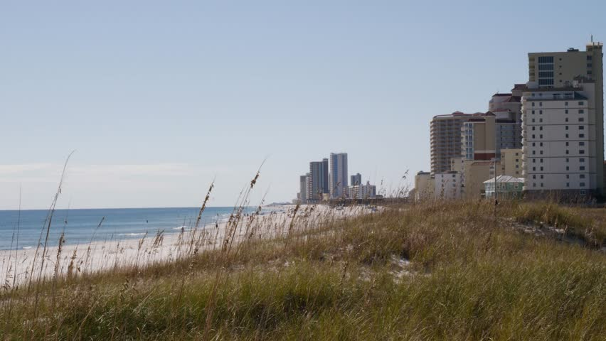 Static shot of modern residential buildings and hotels on the seashore against clear blue sky in a tranquil sunny day