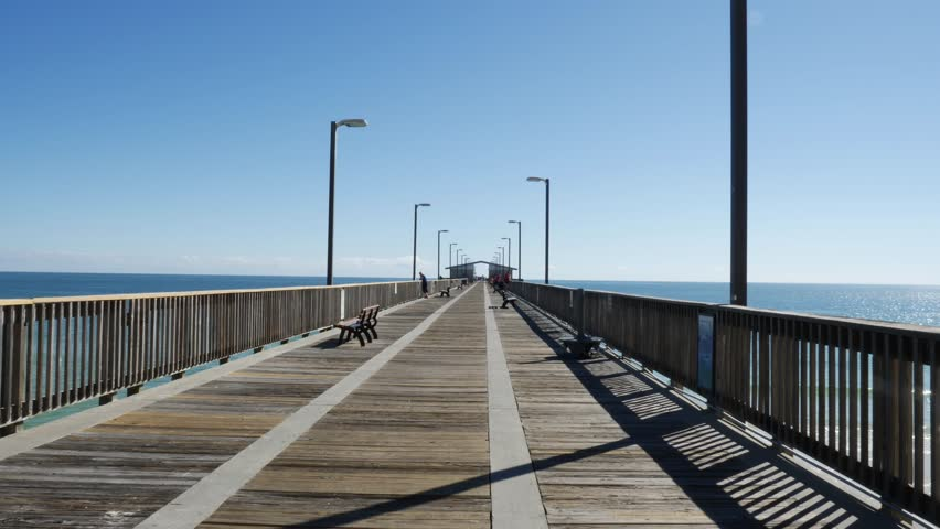 Inspirational static shot of an old and large wooden pier over the sea in a sunny day with clear blue sky