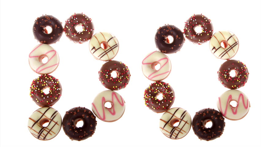 HD Video of many miniature candy coated donuts arranged to spell the word DONUTS. Panning from left to right across the word, isolated on white background.