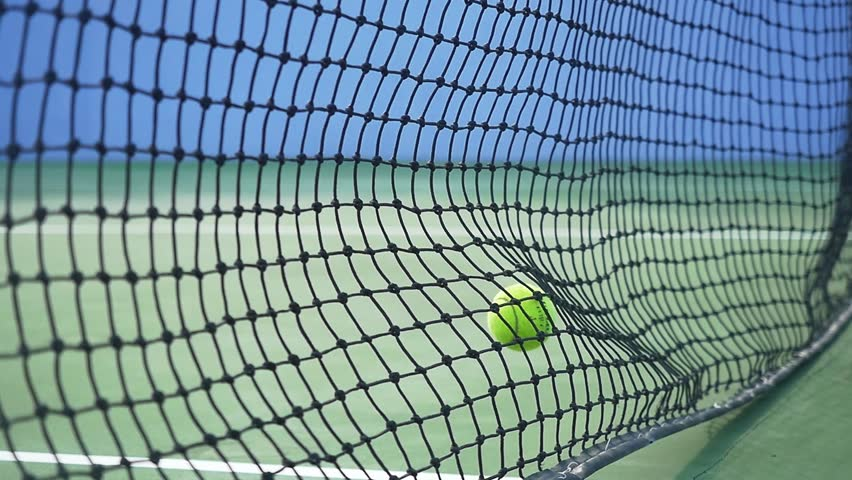 Tennis ball hits the grid falling on a tennis court in sunny day in slow motion. 1920x1080