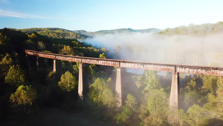 WEST VIRGINIA - CIRCA 2010s - Beautiful aerial over a steel railway trestle in the fog in West Virginia Appalachian mountains.