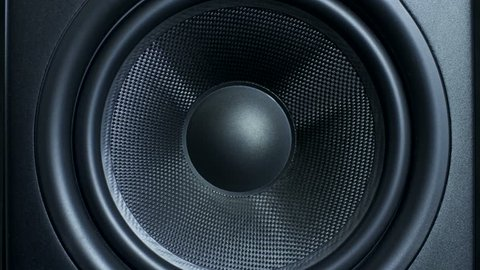 Close-up of black round audio speaker pulsating and vibrating from sound on low frequency. Contemporary stylish sub-woofer.