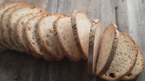 Sliced sourdough bread falling on a table. Shot with high speed camera, phantom flex 4K. Slow Motion.