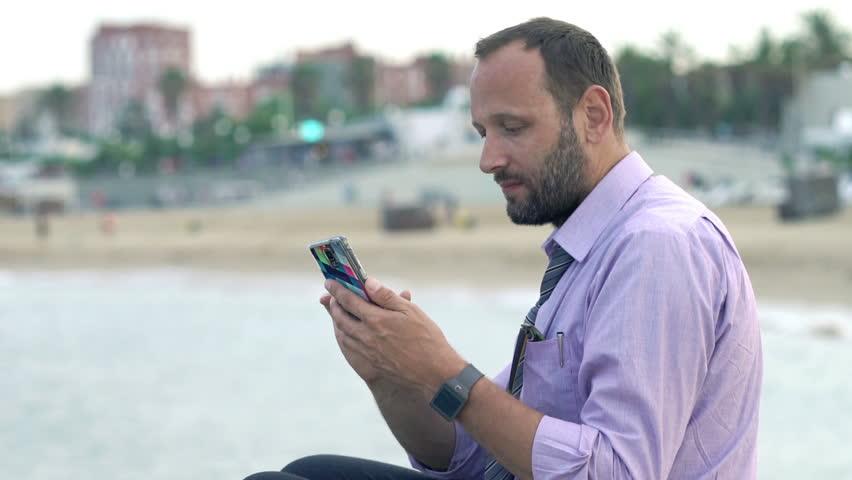 Happy businessman taking selfie photo with cellphone sitting on rock near sea   | Shutterstock HD Video #1006754089