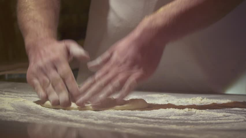 Making pizza or pide dough by close up male hands in pastry kitchen. Shaping dough is precursor to making a wide variety of food stuffs, particularly breads, biscuits, cakes, cookies, dumplings, pasta
