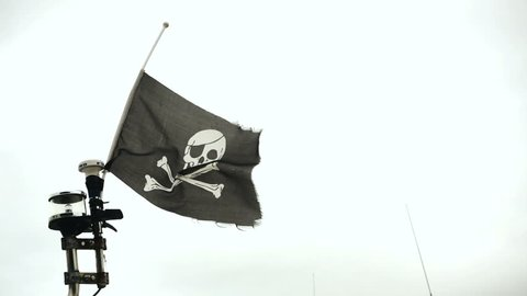 Waving black flag with skull and crossbones symbols over cloudy sky, Jolly Roger pirate flag waving slow motion 240 FPS