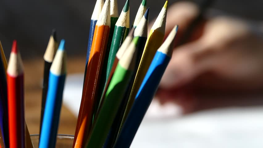 Color pencils in a writing-glass. Draw with colored pencils on white paper and a wooden table. Wooden retro table.