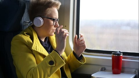 Pretty woman listening music in headphones on smartphone riding train, beautifull girl rides a city bus