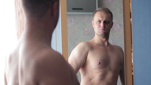 The guy is adorable looking in the mirror. A young man strains his muscles and loves himself