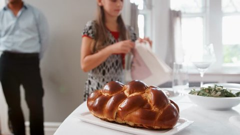 Girl brings and covers challah bread on table for Shabbat