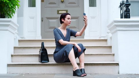 Stylish Woman Sitting On Steps Of Building Taking Selfie