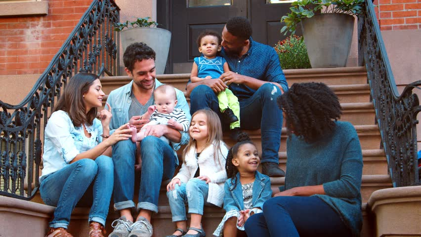 Two families with kids sitting on front stoop in Brooklyn