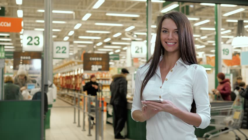 Woman shopping food in supermarket background. Close up view girl buy products using digital gadget in store. Hipster at grocery using smartphone. Person comparing the price in front of cashbox line