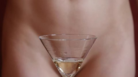 Beautiful young woman without panties pours champagne in glasses in a dark. close-up buttocks and hip