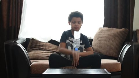 Cute mixed boy doing bottle flip challenge at home and after making dab. Children have a fun. African american kids bottle fun.