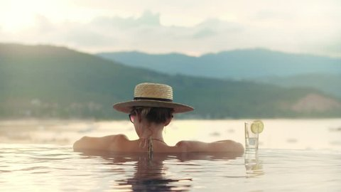 Attractive woman relaxing in edge pool in luxury spa resort with sea view