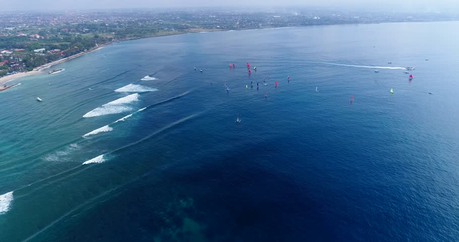 Drone footage of boats participating at a jukung race in Sanur, they are navigating along the beach with their colorful sails, waves are breaking on the shallow reef. | Shutterstock HD Video #1007033629