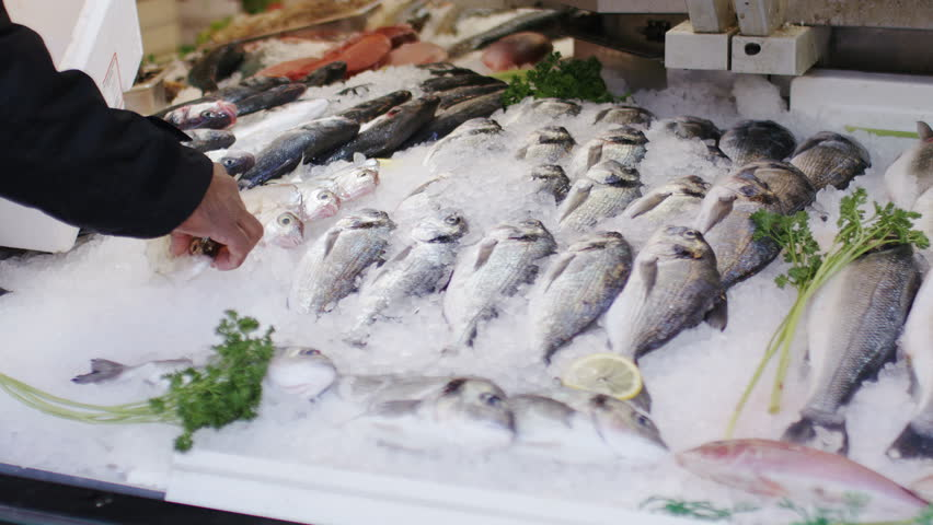 Shop keeper putting fish on display