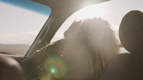 Woman passenger listening to music in car and dancing / Hanksville, Utah, United States