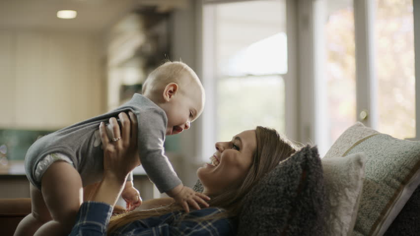 Mother laying on sofa lifting and playing with baby daughter / Alpine, Utah, United States | Shutterstock HD Video #1007046079