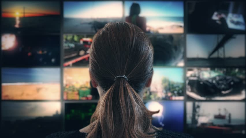 Watching TV Multi Screen Television. Head shot of a ponytail woman watching many videos in a wall of televisions
