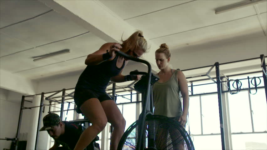 Fitness woman spinning on stationary bike in gym with personal coach. Strong female athlete doing indoor cycling during gym training class.