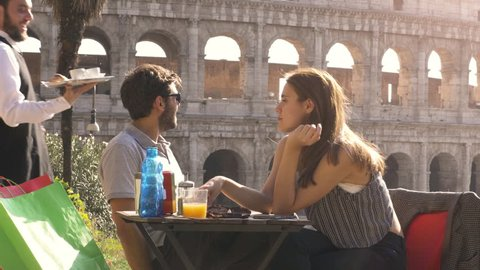 Elegant smiling waiter serving breakfast with coffee croissant cappuccino juice on a try outdoor to young happy couple in a bar restaurant table in front of colosseum in rome at sunset