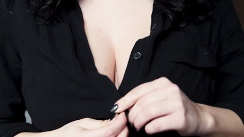 Busty woman button up black shirt on her breasts close up concept of sexual refusal slow motion