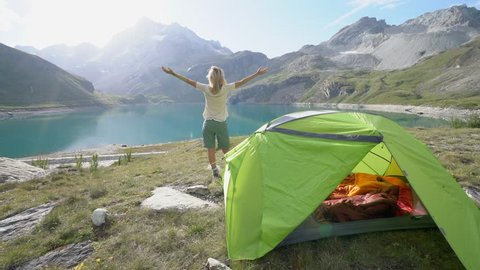Young woman on a hike stands by her tent near stunning mountain lake arms outstretched. Hiker arms wide open in nature surrounded by scenic mountain lake landscape. Success at mountain top