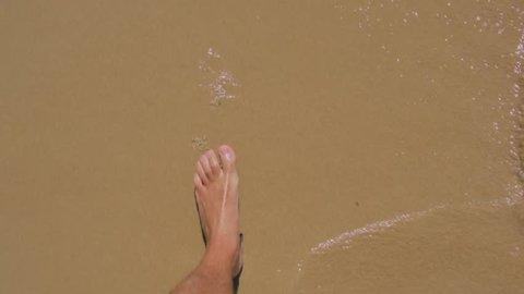 Man walking bare foot on sandy beach in slow-motion