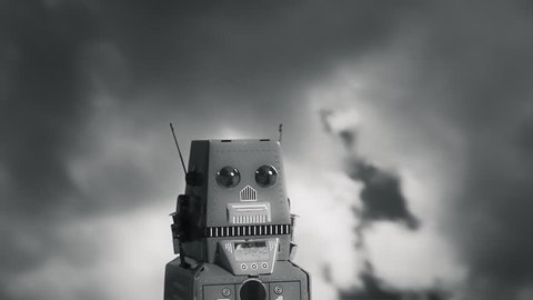 A tin toy robot standing still in front of dark ominous clouds. Film noir style.