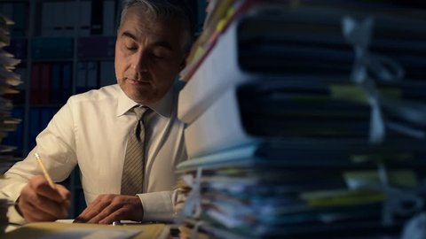 Businessman overloaded with work, he is sitting at office desk and working overtime late at night, his desk is covered with paperwork