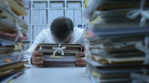 Frustrated overworked office worker hitting his head on a pile of paperwork: stress and work overload concept
