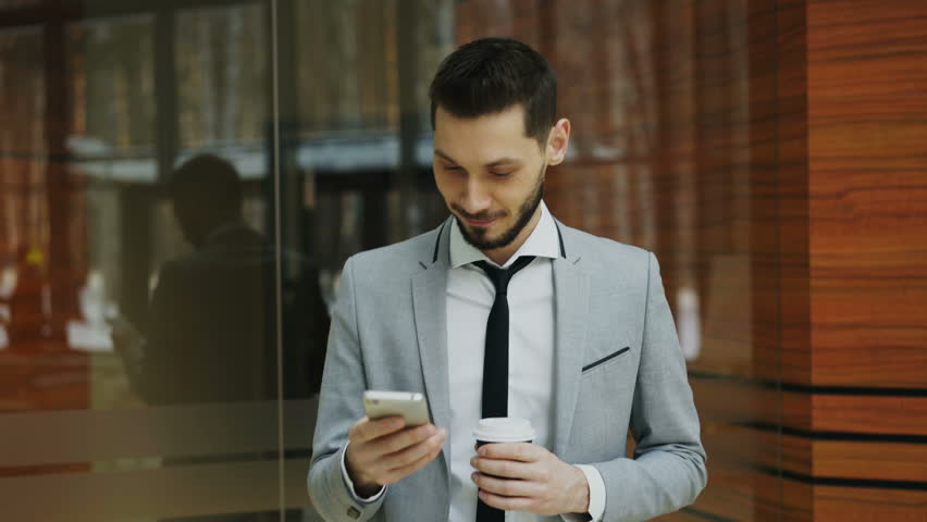 Stedicam shot of cheerful businessman talking with smartphone and walking in modern office hall | Shutterstock HD Video #1007137099