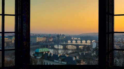 Timelapse of Prague skyline cityscape starting at the sunset ending at night as seen from a window camera moving out the house footage in 4K. Aerial view.
