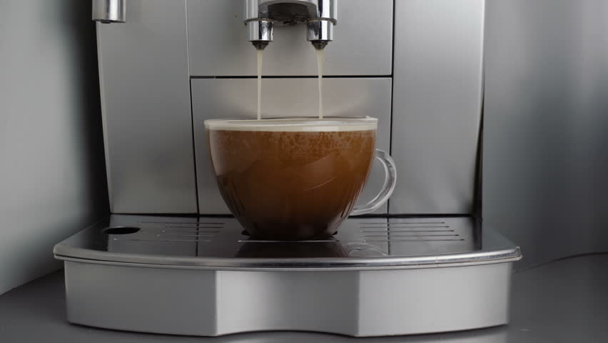 Black coffee is poured from the coffee machine to a glass. Video footage of pouring black coffee.