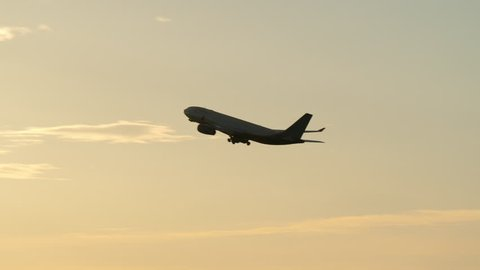 Airplane gaining height after taking off. Silhouette of jet flying at sunset against golden sky and bright sunlight